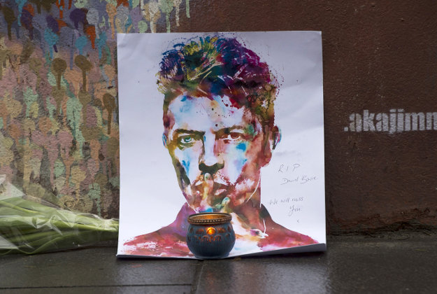 A painting and a candle are left below a mural of David Bowie on the wall of a Morley's store in Brixton, London, the singers birthplace, after the rock star died following an 18-month battle with cancer.