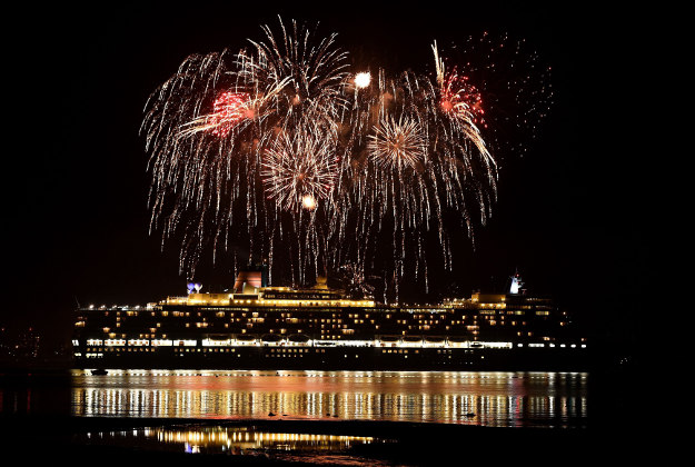 Fireworks are let off as Cunard's Queen Elizabeth, one of the Three Queens liners, makes her way down Southampton water into the River Solent on her first world voyage of 2016. Queen Victoria and Queen Mary 2 also leave the same port for their first world voyage of 2016.