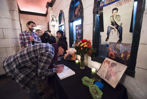 """Fans sign a tribute book for legendary David Bowie as they wait to hear collaborators Tony Visconti and Mick """"Woody"""" Woodmansey bring their acclaimed group Holy Holy performing Bowie's 1970 album The Man Who Sold The World in its entirety in Toronto on Tuesday, Jan. 12, 2016. Bowie, the chameleon-like star who transformed the sound and the look of rock with his audacious creativity and his sexually ambiguous makeup and costumes, died of cancer Sunday."""
