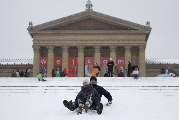 A couple sleds down the steps of the Philadelphia Museum of Art during a snowstorm, Saturday, Jan. 23, 2016, in Philadelphia.