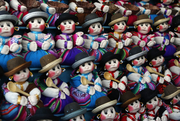 """A woman sells miniature rag dolls in the likeness of """"cholitas"""" at the Alasita Fair in La Paz, Sunday, Jan. 24, 2016. Following ancient Aymara indigenous tradition, """"Alasita"""" is an Aymaran word that means """"buy me,"""" and is the name of the annual fair where people buy miniature items that represent things they hope to attain within the year. People buy the cholita dolls for decoration."""
