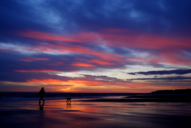 A woman walks her dog before sunrise on Whitley Bay beach, Tyne and Wear.