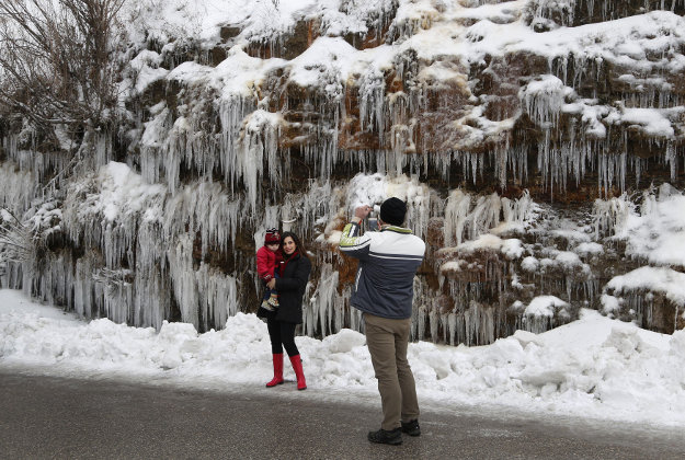 A Lebanese man, right, takes pictures of his wife and daughter, left, as they stand in front of icicles hanging on stones, in Mdeirej village, mount Lebanon, Monday, Jan. 25, 2016. A snow storm is currently hitting Lebanon isolating dozens of villages and cutting the highway linking Beirut with the Syrian capital of Damascus. Schools and day cares were also closed because of the storm, one of the strongest to his Lebanon this winter.