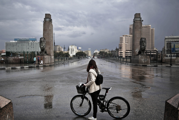 """A 27-year old Egyptian artist stops with her bicycle in front of the Kasr Al Nile bridge that leads to Tahrir Square, after making her way back from the square, during the fifth anniversary anniversary of the 2011 uprising, in Cairo, Egypt, Monday, Jan. 25, 2016. """"The anniversary of Jan. 25 2011 does not represent a single moment, but the start of an ongoing movement. This affected everything from the big things to the little things – such as giving me the push that I needed to ride my bike as a woman in Egypt. We have a different understanding now of public spaces and of our streets and that cannot be undone – no matter how hard they try,"""" says the young artist."""