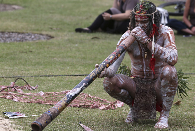 An Aboriginal man plays a didgeridoo during Australia Day in Sydney, Australia, Tuesday, Jan. 26, 2016. Australia Day is the anniversary of the arrival and landing of the First Fleet of convict ships from Great Britain, and the raising of the Union Jack at Sydney Cove by Captain Arthur Phillip, on Jan 26, 1788.
