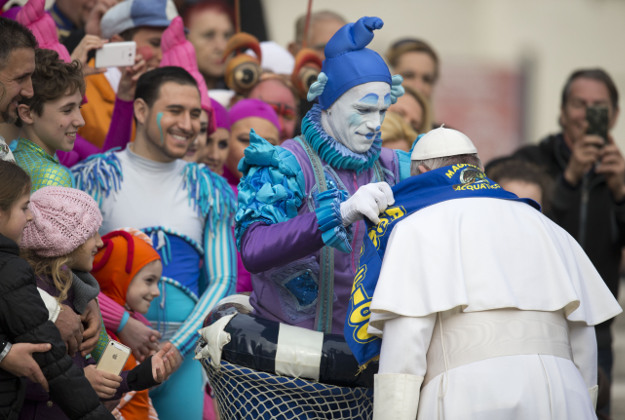 Circus artists who performed for Pope Francis during his weekly general audience give him a scarf of their circus, in St. Peter's Square, at the Vatican, Wednesday, Jan. 27, 2016