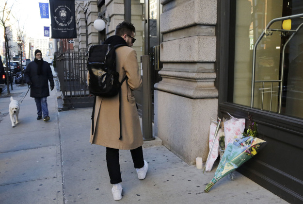 A man pauses to look at bouquets of flowers in front of the building where David Bowie had his New York apartment, Monday, Jan. 11, 2016. Bowie, the other-worldly musician who broke pop and rock boundaries with his creative musicianship, nonconformity, striking visuals and a genre-spanning persona he christened Ziggy Stardust, died of cancer Sunday. He was 69.