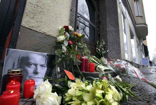 Flowers and a portrait are placed in front of the apartment building where David Bowie once lived in Berlin, Germany, Monday, Jan. 11, 2016, to honor the British musician.