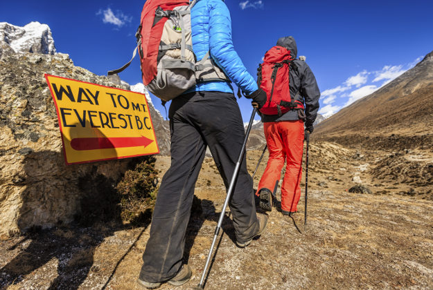 Group of trekkers passing signpost on way to Mount Everest Base Camp - Mount Everest (Sagarmatha) National Park.