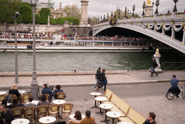 People enjoying a coffee on the banks of the Seine, Paris.