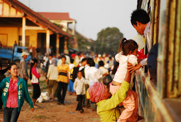 A passenger getting onto a train in Cambodia in the handiest way