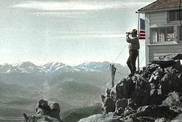 A photo taken in approximately 1916 in Rocky Mountain National Park in the USA, featuring Ranger Kesner at the Twin Sisters Peaks fire outlook.
