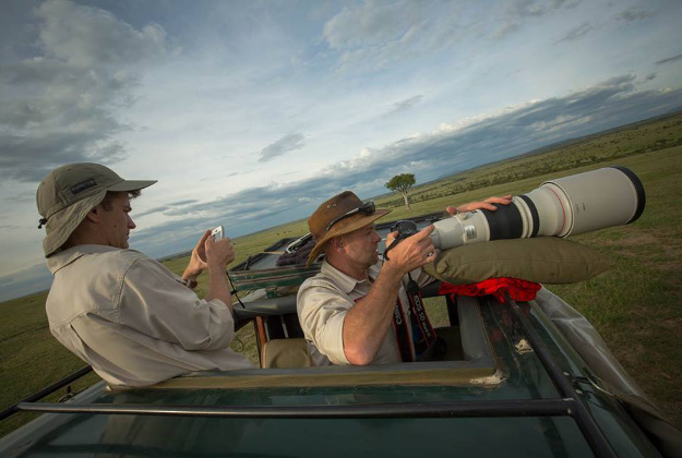 In a photpgraph taken by Make It Kenya 07 January 2016, Andre Van Kets (left) and Carel Verhoef, creators of the website HerdTracker, an online resource which tracks and documents east Africa's great wildebeest migration, prepare to stream a live broadcast on the Periscope application.