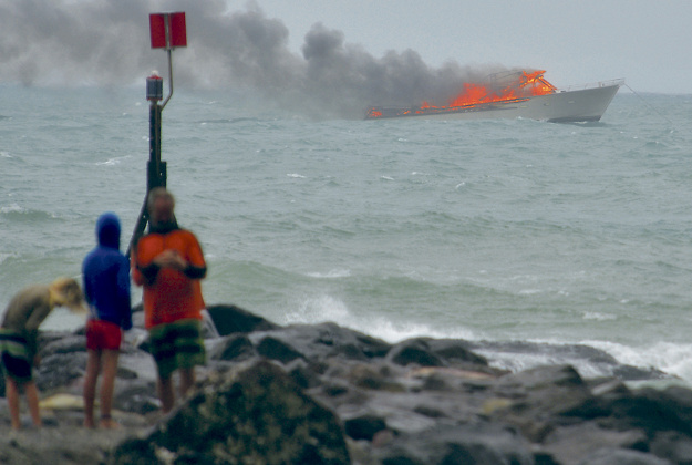 eople stand on the shoreline as a tourist boat carrying 60 people burns out at sea off the coast of Whakatane, New Zealand, Monday, Jan 18, 2016.