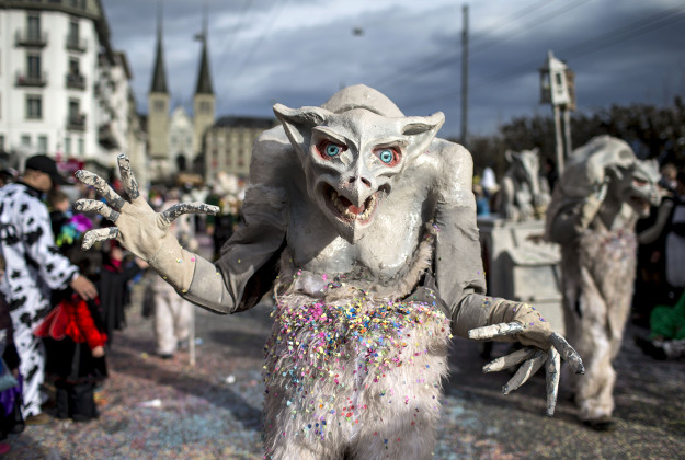 Masked revelers parade through the streets during the start of the carnival in Lucerne, Switzerland, Monday, Feb. 8, 2016.