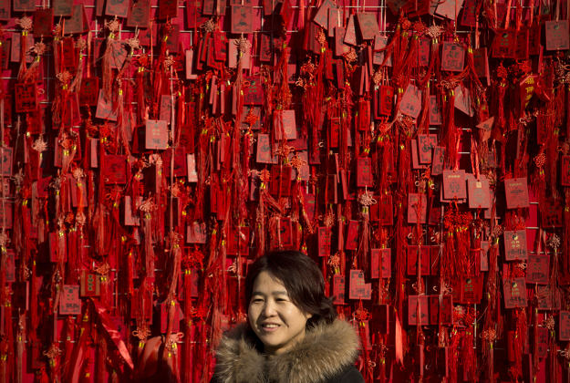 A woman stands in front of a fence covered in blessing tablets at the Dongyue Temple during the second day of the Chinese Lunar New Year in Beijing, Tuesday, Feb. 9, 2016. Millions of Chinese are celebrating the Lunar New Year, which marks the Year of the Monkey on the Chinese zodiac.