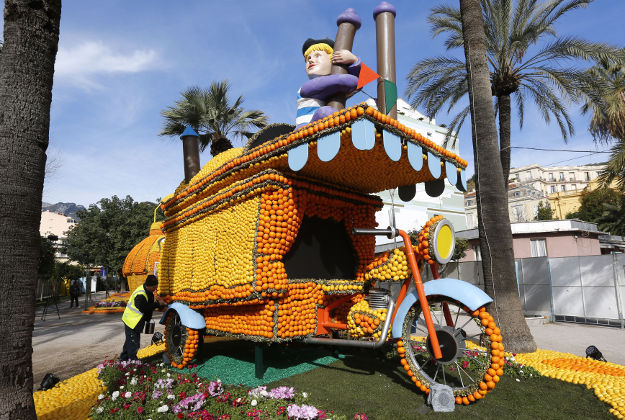 "A worker sets up a giant sculpture decorated with oranges and lemons during the 83th Lemon festival in Menton, southeastern France, Thursday. The festival will tribute Italian cinema ""Cinecitta"" from February 13th to March 2nd."