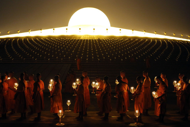 Thai Buddhist monks hold candles as they gather at Wat Dhammakaya temple to participate in Makha Bucha Day ceremonies, in Pathum Thani province, Thailand, Monday, Feb. 22, 2016. Makha Bucha, a religious holiday that marks the anniversary of Lord Buddha's mass sermon to the first 1,250 newly ordained monks 2,559 years ago.