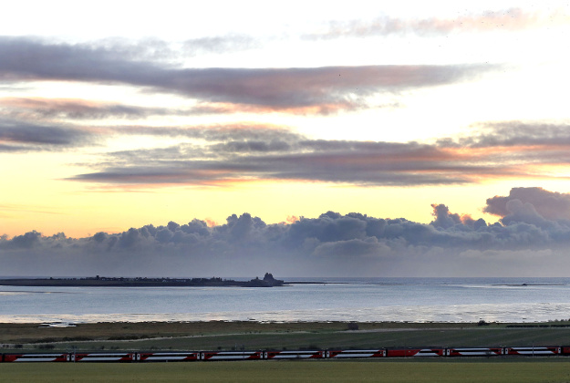 A Virgin Trains service on the East Coast main line passes Holy Island off the coast of Northumberland.