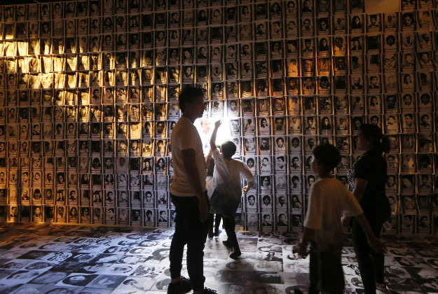 "Children walk through walls of portraits of victims under the 20-year-rule of the late strongman Ferdinand Marcos during the opening of the ""experiential museum"" to coincide with the 30th commemoration of the ""People Power Revolution"" that ousted the Marcoses from power and helped install Corazon ""Cory"" Aquino to the presidency Wednesday, Feb. 24, 2016 at suburban Quezon city northeast of Manila, Philippines. The Holocaust-type museum was conceived to remind the young generation of the abuses and human rights violations perpetrated under years of Martial Rule in the country.("