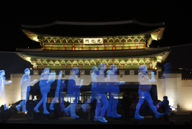 Holograms of protesters are shown on the screen during a holographic demonstration called 'ghost protest', demanding freedom of assembly and guarantee the right to peaceful assembly, in front of the Gwanghwamun, the main gate of the 14th-century Gyeongbok Palace, one of South Korea's well known landmarks, in Seoul, South Korea, Wednesday, Feb. 24, 2016. Protesters appeared on a screen 10 meters long and 3 meters wide in a rally organized by Amnesty International Korea.