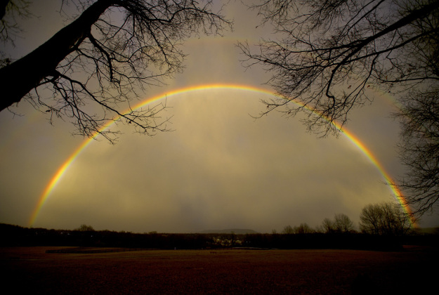 A full rainbow arches over Tom Tudek Memorial Park with Mount Nittany below, in State College, Pa., Wednesday, Feb. 24, 2016.