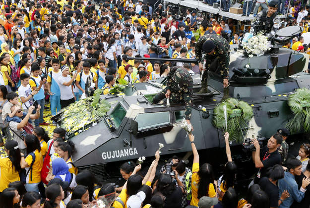"Students hand flowers to soldiers during the 30th anniversary celebration of the ""People Power Revolution"" that toppled the 20-year-rule of the late strongman Ferdinand Marcos and helped install Corazon ""Cory"" Aquino to the presidency Thursday, Feb. 25, 2016 at suburban Quezon city northeast of Manila, Philippines. The four-day People Power saw hundreds of thousands of Filipinos trooping to EDSA Avenue fronting two military camps to lend support to mutinous soldiers who broke away from Marcos."