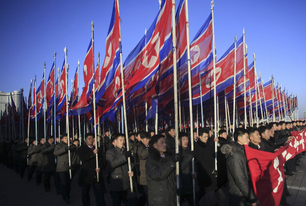 """North Koreans parade with the North Korean flag in Kim Il Sung Square in Pyongyang, North Korea, Thursday, Feb. 25, 2016, to show their loyalty to the Workers' Party. North Korea is massing its people to hunker down and work harder with a new """"70-day campaign of loyalty"""" in the run up to a major meeting of its ruling Workers' Party in May."""