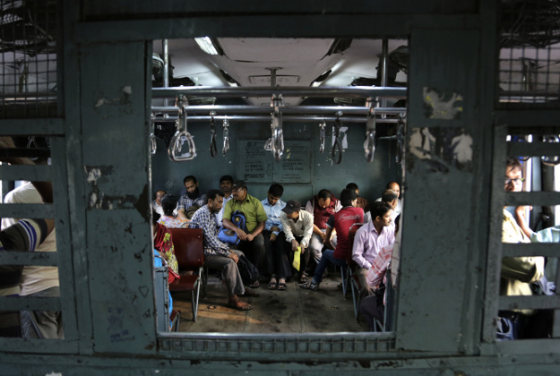 Indian commuters board a reserved compartment of a train at the railway station in Allahabad, India, Thursday, Feb. 25, 2016. Indian railway minister Suresh Prabhu Thursday unveiled the budget for one of the world's largest railways network that serves more than 23 million passengers a day. Once a pride of the Indian government, it's now hobbled by ageing infrastructure.