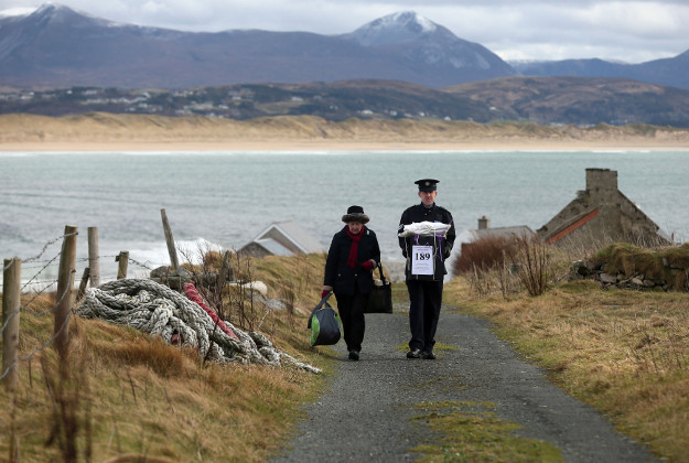 Presiding Officer Carmel McBride and Garda Sergeant Paul McGee carry a ballot box away from a polling station after voting concluded on the island of Inishbofin. Voters on the remote isle off the coast of Donegal were among the first to cast their ballots in Ireland's General Election, a day ahead of the rest of the country.