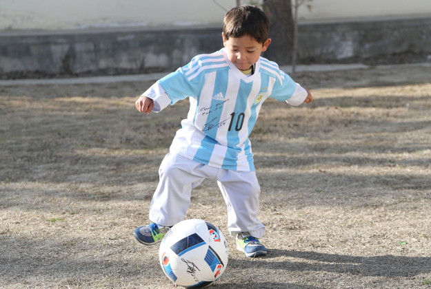 In this provided by UNICEF, Murtaza Ahmadi, an Afghan Lionel Messi fan, wears a donated and signed shirt by Messi, in Kabul, Afghanistan, Thursday, Feb. 25, 2016.