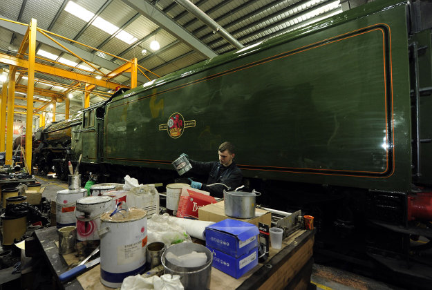 The green livery is applied to the Flying Scotsman, ahead of its official return to steam next week, in a workshop at the National Railway Museum in York. Image by: John Giles/PA Wire.