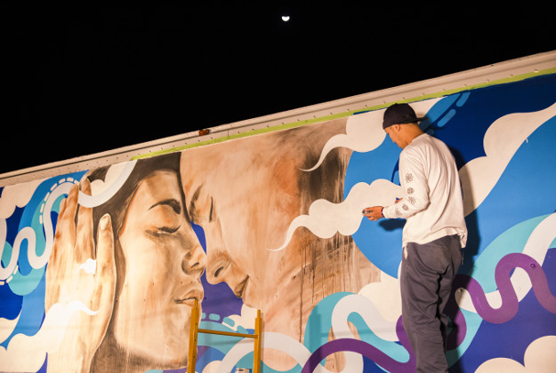 Street artists paint a Hawaiian Airlines service vehicle.