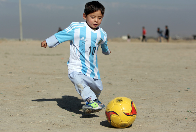 Murtaza Ahmadi, a five-year-old Afghan Lionel Messi fan plays with a soccer ball during a photo opportunity as he wears a shirt signed by Messi, in Kabul, Afghanistan