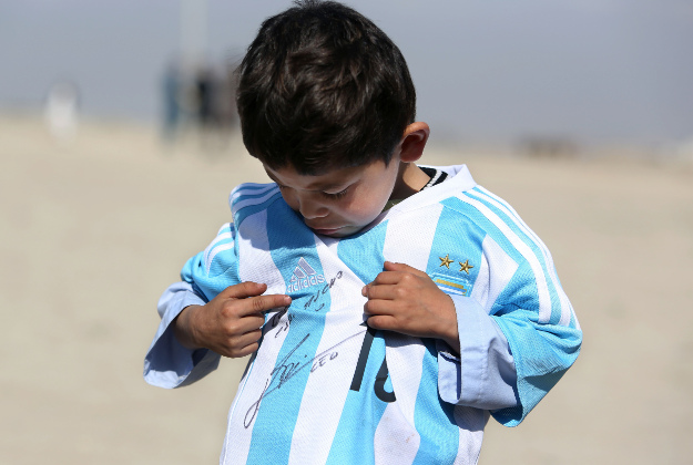 Murtaza Ahmadi, a five-year-old Afghan Lionel Messi fan poses for photograph, as he wears a shirt signed by Messi.