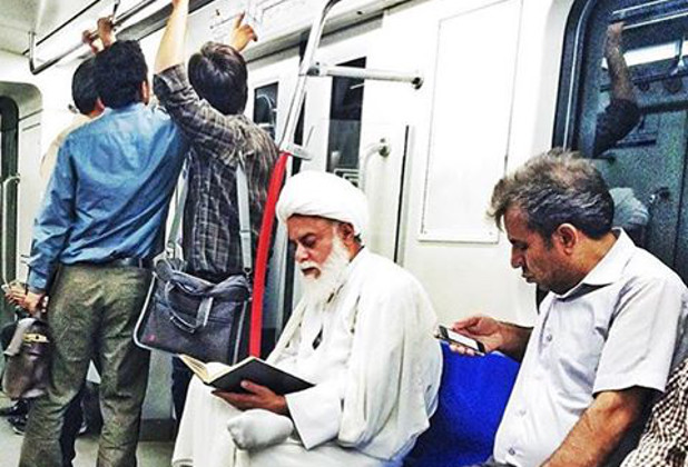 A cleric reads a book on the metro
