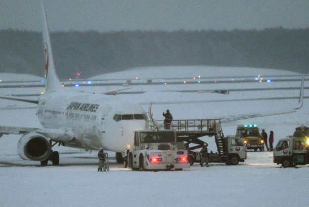 A Japan Airlines Boeing 737 sits on the snow-covered tarmac after more than 160 passengers and crew slid down emergency chutes in snow due to an engine fire at New Chitose Airport in Sapporo in Hokkaido, Japan's northernmost main island.