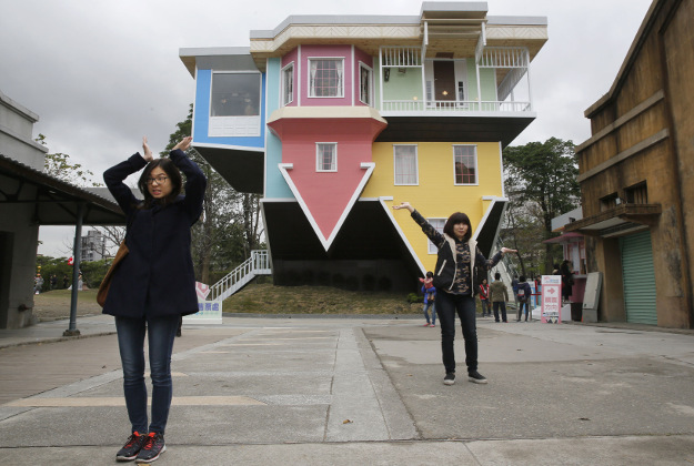 Visitors pose outside of an upside-down house created by a group of Taiwanese architects at the Huashan Creative Park in Taipei, Taiwan.