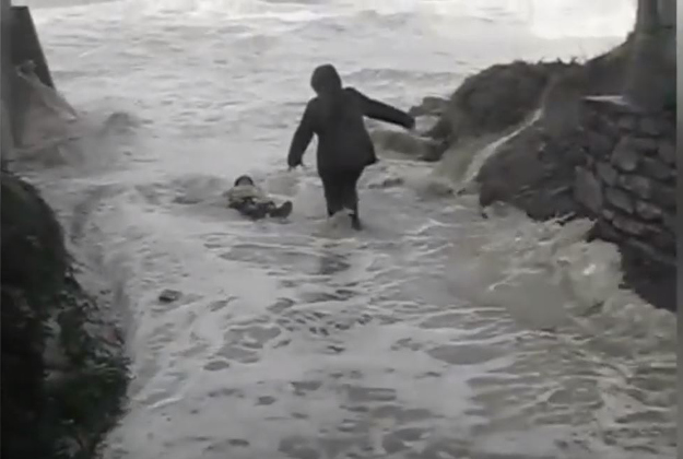 The moment an elderly couple were dragged into the water by a giant wave