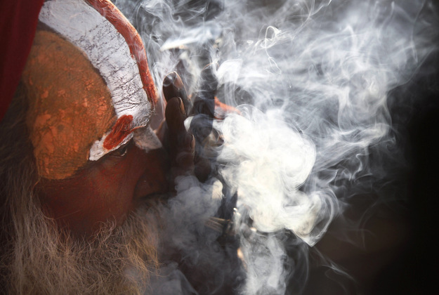 "A Hindu holy man smokes marijuana at the courtyard of the Pashupatinath temple during ""Shivaratri"" festival in Kathmandu, Nepal, Monday, March 7, 2016. ""Shivaratri,"" or the night of Shiva, is dedicated to the worship of Lord Shiva, the Hindu god of death and destruction."
