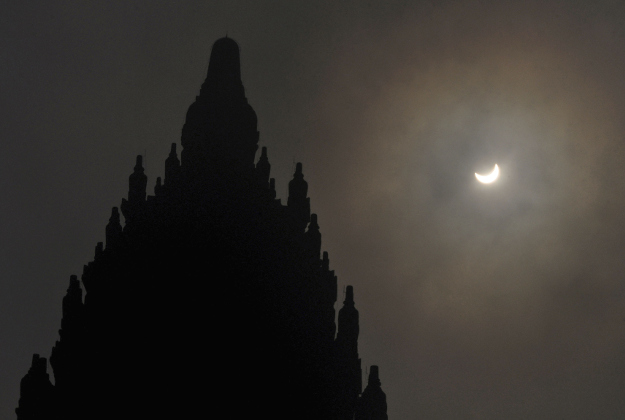 A partial solar eclipse is seen behind the 9th century Prambanan Temple in Yogyakarta, Indonesia, Wednesday, March 9, 2016. The rare astronomical event is being witnessed Wednesday along a narrow path that stretches across 12 provinces encompassing three times zones and about 40 million people.