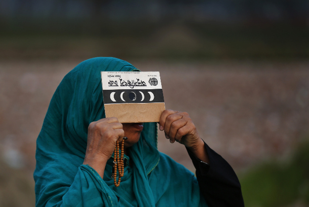 A Bangladeshi Muslim woman watches a partial solar eclipse in Dhaka, Bangladesh, Wednesday, March 9, 2016. Bangladeshi and Indian people in northeast and eastern coastal strip of the sub-continent viewed a partial solar eclipse as a total eclipse of the sun unfolded over Indonesia on Wednesday, briefly plunging cities into darkness and startling wildlife.