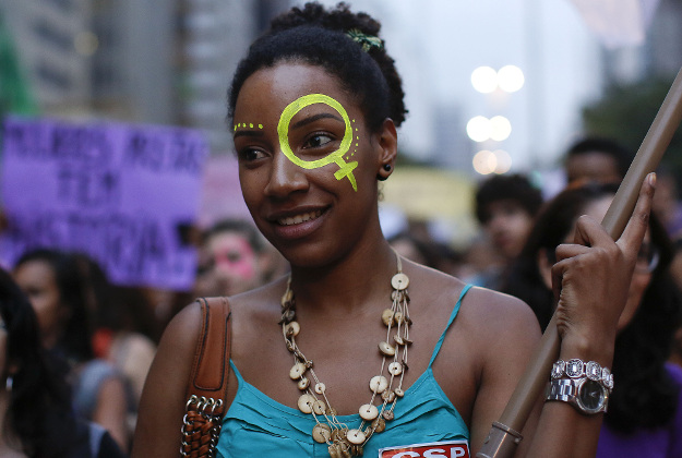 An activist attends a demonstration to mark International Women's Day, in Sao Paulo, Brazil, Tuesday, March 8, 2016. International Women's Day celebrated women and their accomplishments, but it also offered a stark reminder of the gender divides in rights, representation and pay.