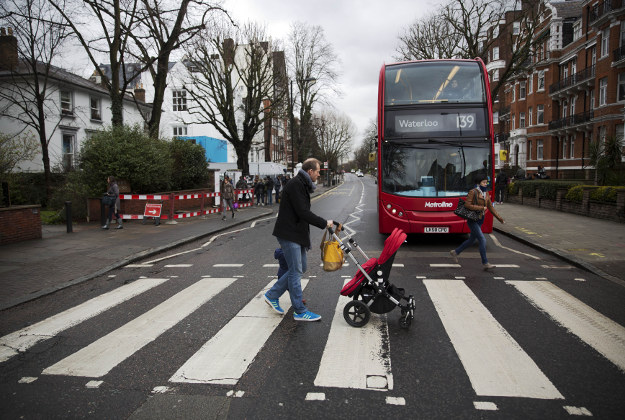 People walk over the zebra crossing where the cover picture of the Beatles' Abbey Road album was taken outside Abbey Road studios in London, Wednesday, March 9, 2016. George Martin, the Beatles' urbane producer who quietly guided the band's swift, historic transformation from rowdy club act to musical and cultural revolutionaries, has died, his management said Wednesday. He was 90.