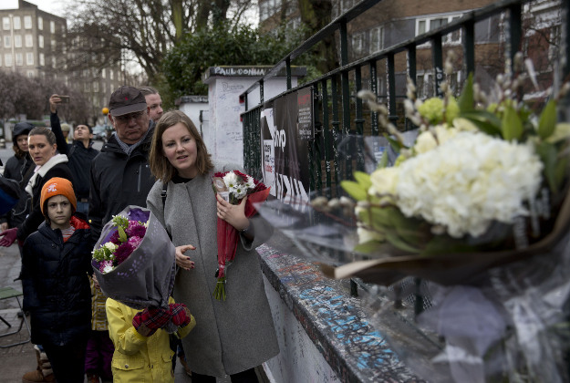 Tourists from Finland place flowers in memory of George Martin, the Beatles' producer, outside Abbey Road studios where the Beatles recorded albums and where the zebra crossing cover picture of the Abbey Road album was originally taken in London, Wednesday, March 9, 2016. George Martin, the Beatles' urbane producer who quietly guided the band's swift, historic transformation from rowdy club act to musical and cultural revolutionaries, has died, his management said Wednesday March 9, 2016. He was 90.