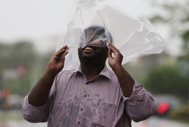 A man covering his head with a plastic bag enjoys walking under the rain in Dubai, United Arab Emirates, Wednesday, March 9, 2016. Heavy rains have closed Abu Dhabi's international airport and shut schools in the United Arab Emirates.