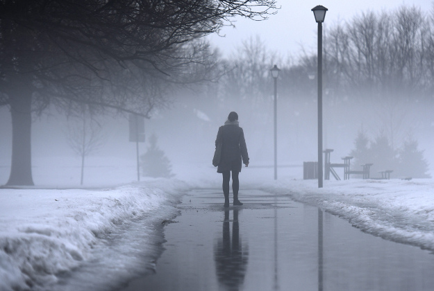 A woman walks in Brewer Park as heavy fog rises on Wednesday, March 9, 2016 in Ottawa.