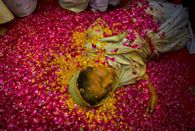 An Indian Hindu widow lies on a bed of flower petals during Holi celebrations at the Gopinath temple, 180 kilometres (112 miles) south-east of New Delhi, India Monday, March 21, 2016. A few years ago this joyful celebration was forbidden for Hindu widows. Like hundreds of thousands of observant Hindu women they would have been expected to live out their days in quiet worship, dressed only in white, their very presence being considered inauspicious for all religious festivities.