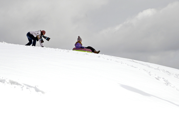 Ronnie Cavener, left, gives Shannon Paul a push as she sleds down a hill, Monday, March 21, 2016, in Andover, Mass.