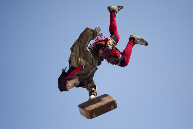An acrobat jumps from the top of a school building during a performance for foreign migrant workers children to celebrate the Purim festival in Tel Aviv, Israel, Tuesday, March 22, 2016. The Jewish holiday of Purim commemorates the Jews' salvation from genocide in ancient Persia, as recounted in the Book of Esther, which is read in synagogues. Other customs include: sending food parcels and giving charity; dressing up in masks and costumes; eating a festive meal; and public celebrations.